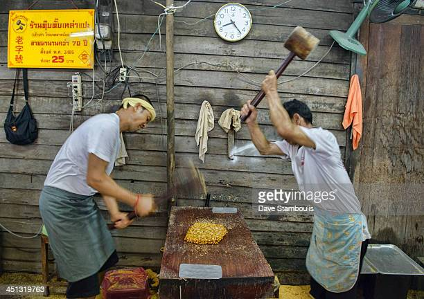 CONTENT] workers pounding peanut brittle at the Vegetarian Festival in Bangkok Thailand