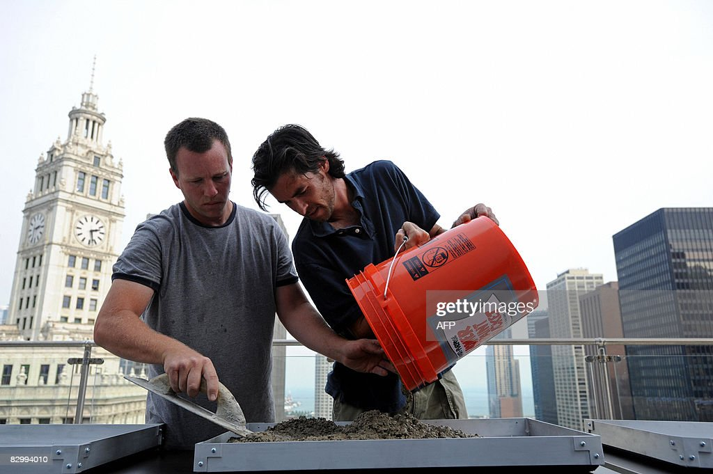 Workers pour cement for real state developer Donald Trump and his children to make hand prints before a press conference at the Trump International Hotel and Tower in Chicago on September 24, 2008. Trump's 1,360-foot (414.5-meter), 92-story tower is expected to be finished in six months and will stand as the second-tallest building in Chicago, after the Sears Tower. AFP PHOTO/Amanda Rivkin