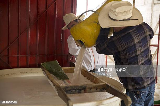 Workers pour honey water extracted from maguey plants through a filter during the cleaning and fermentation process at the Del Razo family's Rancho...