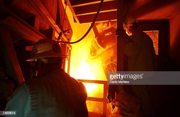 Workers pour molten steel from the furnace into a giant ladle at the TAMCO steel mini mill on October 4 2002 in Rancho Cucamonga California TAMCO...