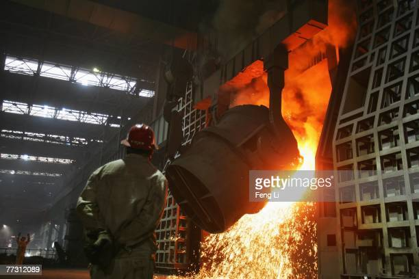 Workers pour the molten iron into the converter in the steelmaking workshop at Chengde Steel Plant on October 11 2007 in Chengde of Heibei province...