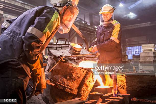 Workers pouring molten metal into moulds in foundry