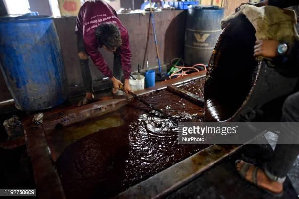 Workers pours Molten Raw Hardened molasses on mud bucket to prepare molasses Chaku at Tokha Kathmandu Nepal on January 10 2020 Molasses Chaku is...