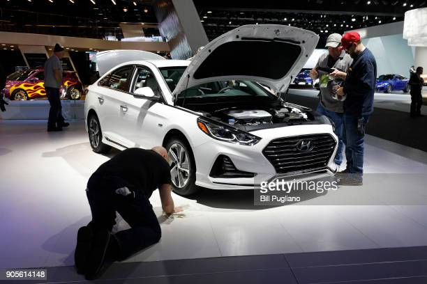 Workers prep around a Hyundai Sonata at the Hyundai 1272exhibit is shown at the 2018 North American International Auto Show January 16 2018 in...