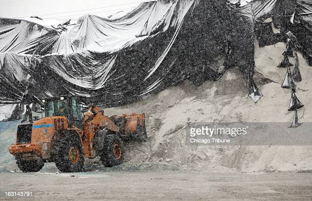 Workers prep for more trucks at the Streets and Sanitation Departments salt storage site at Grand Ave and Rockwell as the snow continues to fall in...