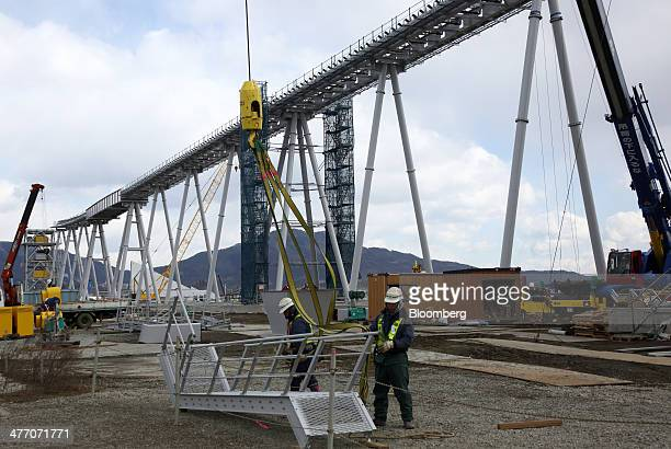 Workers prepare a component for a conveyor carrying excavated soil to a residential area under construction in Rikuzentakata Iwate Prefecture Japan...