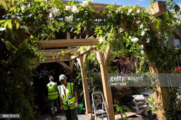 Workers prepare a garden at the RHS Chelsea Flower Show site at Royal Hospital Chelsea on May 16 2017 in London England Preparations are underway for...