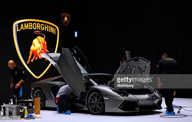 Workers prepare a Lamborghini Aventador LP 700-4 luxury automobile, produced by Automobili Lamborghini SpA, on the company's stand ahead of the...