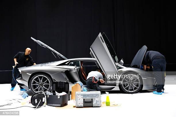 Workers prepare a Lamborghini Aventador LP 7004 luxury automobile produced by Automobili Lamborghini SpA on the company's stand ahead of the opening...