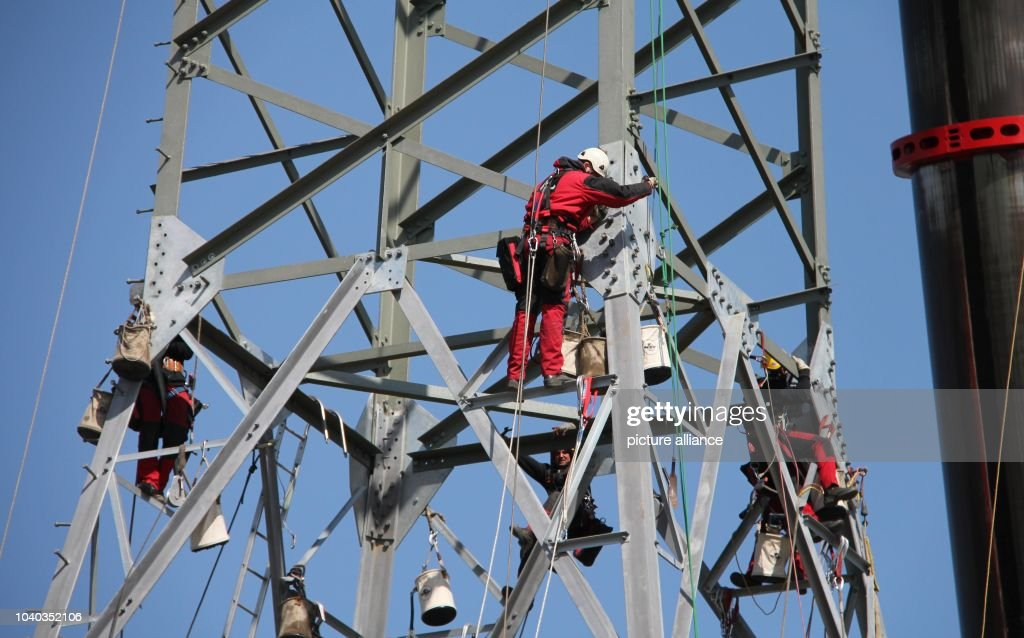 Workers prepare a lattice tower to hang power lines in