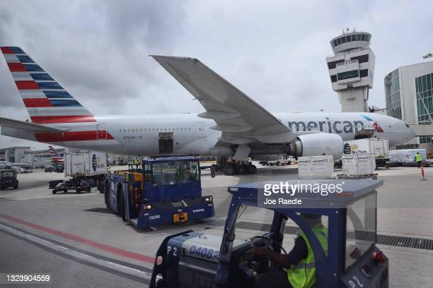 Workers prepare an American Airlines plane at a gate before its flight from the Miami International Airport on June 16, 2021 in Miami, Florida. Miami...