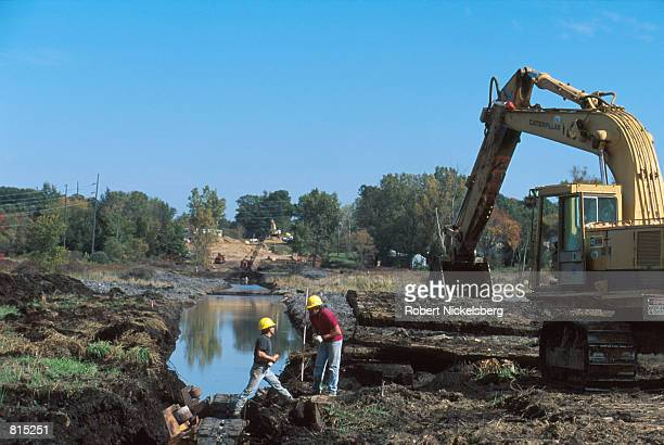 Workers prepare an area of peat bog in a wetlands area for a pipeline that will be submerged there October 3 2000 in Howell Michigan 60 miles north...