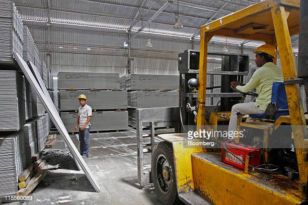 Workers prepare asbestos roofing sheets for dispatch at Everest Industries Ltd's roof factory in Lakhmapur India on Wednesday May 18 2011 India ranks...