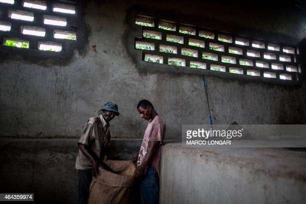 Workers prepare bags of YlangYlang flowers on February 24 2015 in Moroni prior to place them in an large alembic where after hours long distilling...