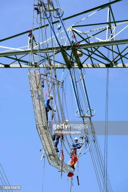 Workers prepare cable up a newly-constructed transmission tower during a construction of 380 kV high voltage transmission line for the high-voltage...