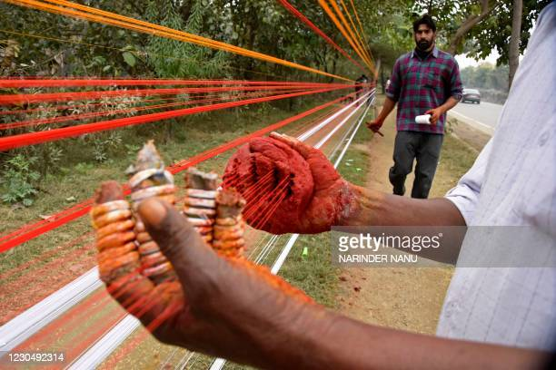 Workers prepare coloured kite threads along the roadside ahead of the Lohri festival on the outskirts of Amritsar on January 9, 2021.