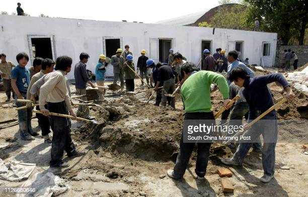 Workers prepare concrete in front of one of the new prefabricated hospital wards that are being built to house SARS patients at the Xiaotangshan...