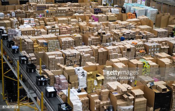 Workers prepare customer orders for dispatch as they work around goods stored inside an Amazon.co.uk fulfillment centre in Peterborough, central...