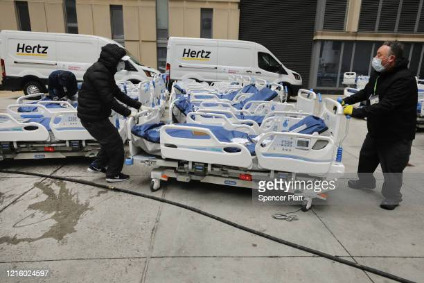 Workers prepare dozens of extra medical beds as they are delivered to Mount Sinai Hospital amid the coronavirus pandemic on March 31 2020 in New York...