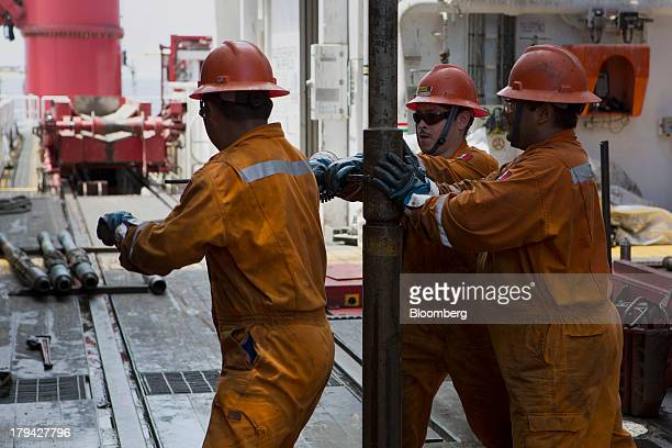 Workers prepare drilling pipe on the Petroleos Mexicanos La Muralla IV deep sea crude oil platform in the waters off Veracruz Mexico on Friday Aug 30...