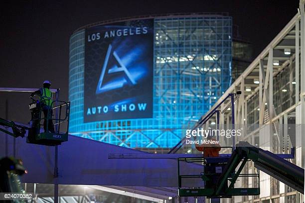 Workers prepare for the public opening of the LA Auto Show at the end of the four-day auto trade show AutoMobility LA at the Los Angeles Convention...