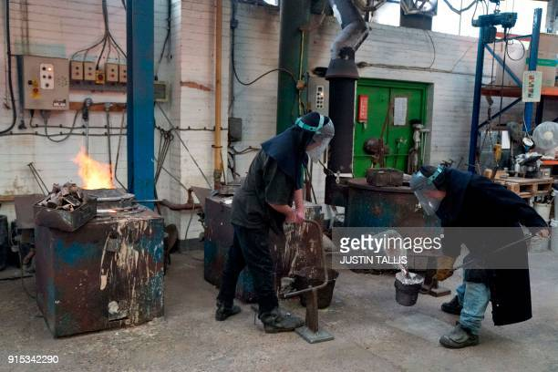 Workers prepare molten bronze before casting BAFTA masks during a photo call at the New Pro Foundries west of London on February 7 2018 ahead of the...