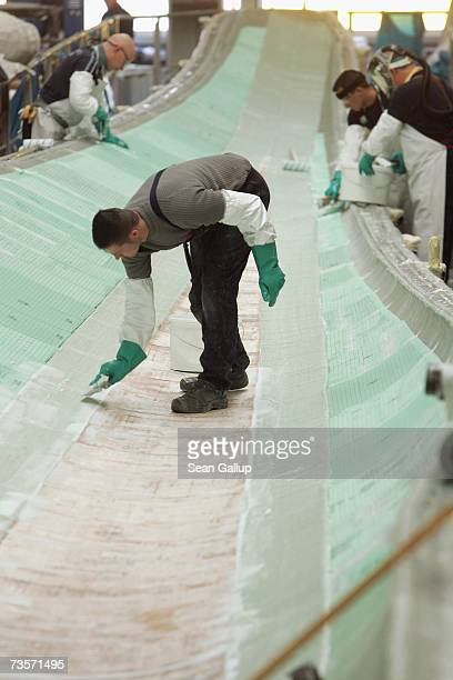 Workers prepare one half of a 45 meter long wind turbine blade which is made of balsa wood and fibre glass and hardened with resin at the Nordex wind...
