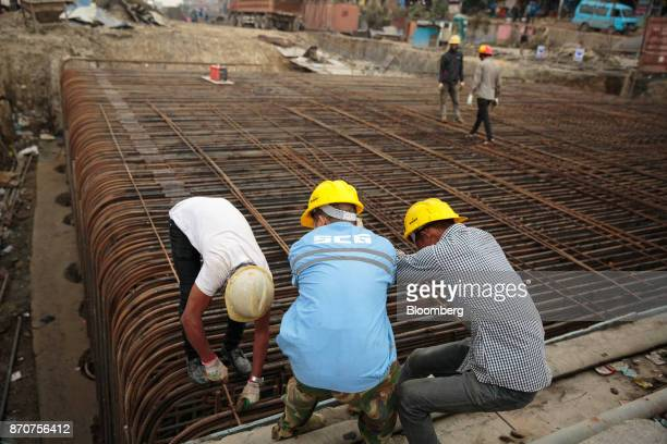 Workers prepare reinforcing steel at a construction site for a road operated by Shanghai Construction Group Co in the Kalanki Chowk area of Kathmandu...