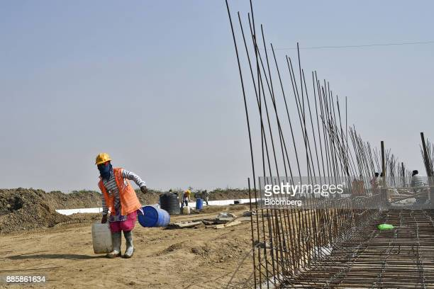 Workers prepare reinforcing steel at an under construction sewerage system on the project site for a 920squarekilometer industrial area located on...