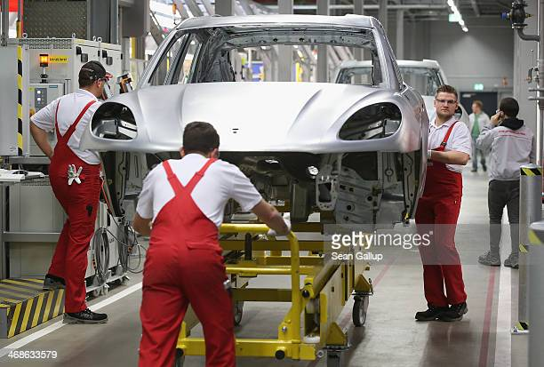 Workers prepare the body of a Porsche Macan SUV at the new Porsche Macan factory at the Porsche plant on February 11, 2014 in Leipzig, Germany....