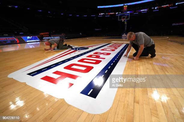 Workers prepare the court before the game between the Kentucky Wildcats against the Monmouth Hawks at Madison Square Garden on December 9 2017 in New...