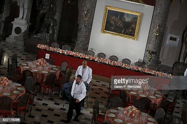 Workers prepare the dining room ahead of a luncheon for US President Donald Trump at the US Capitol January 20 2017 in Washington DC President Trump...