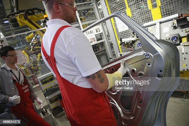 Workers prepare the doors of a Porsche Macan SUV at the new Porsche Macan factory at the Porsche plant on February 11, 2014 in Leipzig, Germany....