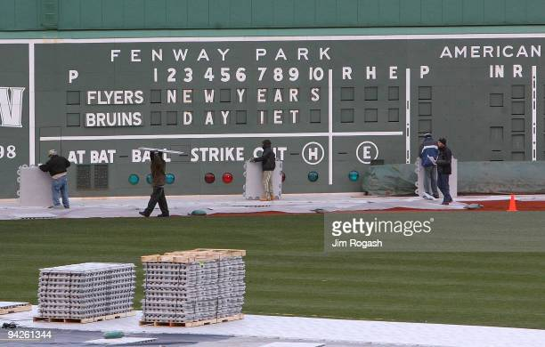 Workers prepare the field for the refrigeration truck that will be used to create the ice for the Bridgestone NHL Winter Classic at Fenway Park on...