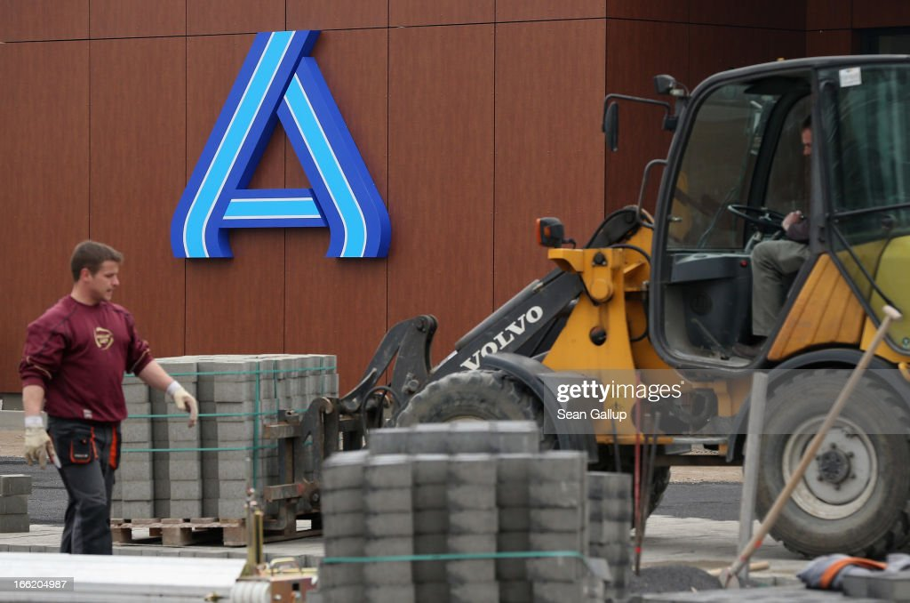 Workers prepare the future parking lot in front of a new Aldi Nord discount supermarket on the 100th anniversary of the chain on April 8, 2013 in Berlin, Germany. Aldi, which today is among the world's most successful discount grocery store chains, will soon mark its 100th anniversary and traces its history back to Karl Albrecht, who began selling baked goods in Essen on April 10, 1913 and founded the Aldi name by shortening the phrase Albrecht Discount. His sons Karl Jr. and Theo expanded the chain dramatically, creating 300 stores by 1960 divided between northern and southern Germany, with Aldi Nord and Aldi Sued, respectively. Today the two chains have approximately 4,300 stores nationwide and have also expanded into other countries across Europe and the USA. Aldi Nord operates in the USA under the name Trader Joe's.