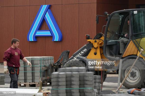 Workers prepare the future parking lot in front of a new Aldi Nord discount supermarket on the 100th anniversary of the chain on April 8 2013 in...