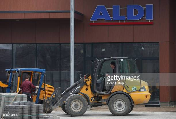 Workers prepare the future parking lot in front of a new Aldi Nord discount supermarket on the 100th anniversary of the chain on April 10 2013 in...