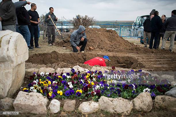 Workers prepare the grave of late former PM Ariel Sharon next to his wife Lili Sharon's grave on January 12 2014 in Havat Hashikmim Israel A memorial...