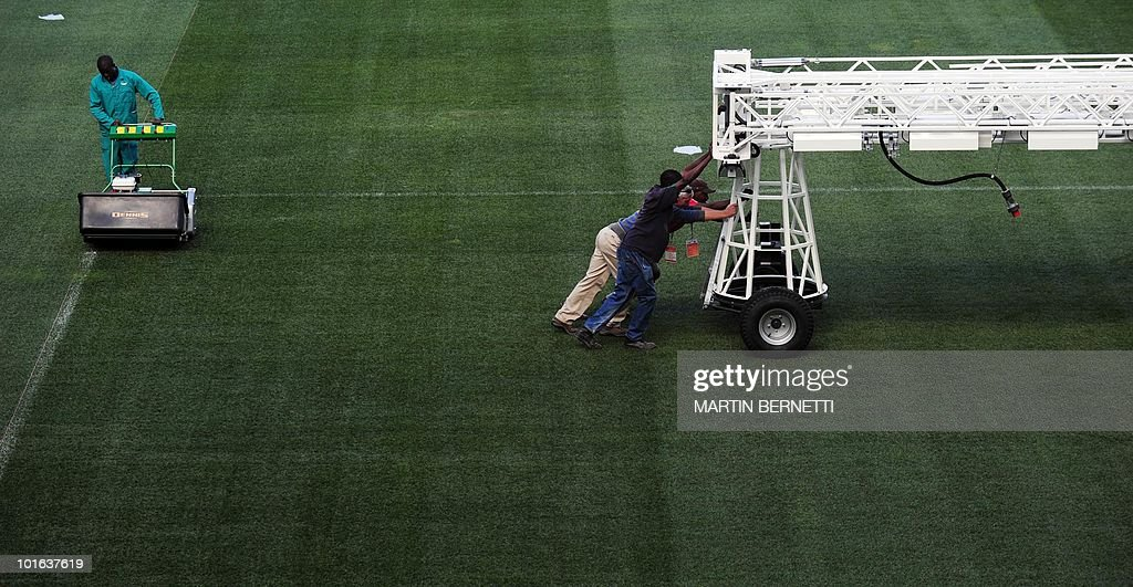 Workers prepare the pitch of the Mbombela Stadium, in Nelspruit on June 5, 2010 in preparation for the start of the FIFA 2010 World Cup. Chile and Honduras will play their first match of the tournament here on June 16. AFP PHOTO / Martin BERNETTI