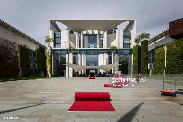 Workers prepare the red carpet before the military honors for the German Chancellor Angela Merkel and Li Keqiang Prime Minister of China on July 09...