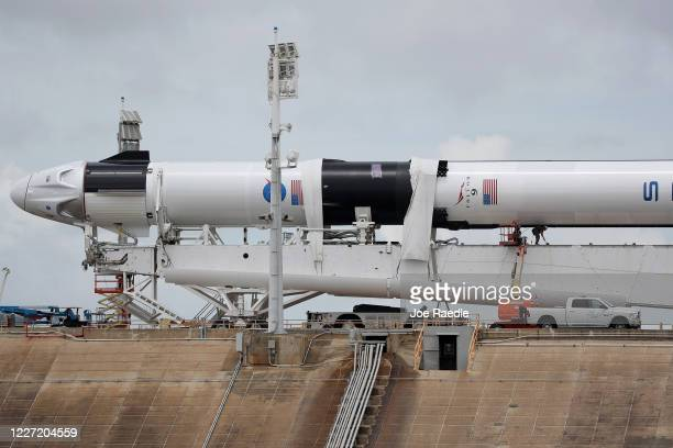 Workers prepare the SpaceX Falcon 9 rocket with the Crew Dragon spacecraft attached for tomorrow's scheduled liftoff from launch pad 39A at the...