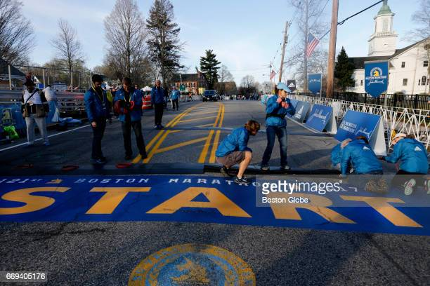 Workers prepare the starting line in Hopkinton Mass on April 17 ahead of the 121st Boston Marathon