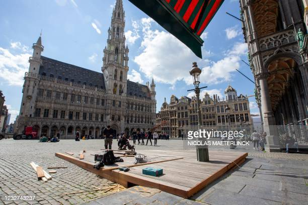 Workers prepare the terrace of a restaurant, at the Brussels Grand Place/ Grote Markt, on May 7 on the eve of the reopening of restaurant and cafe...