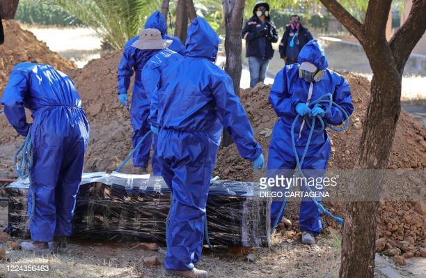Workers prepare to bury the coffin of a COVID-19 victim in a common grave at the general cemetery in Cochabamba, Bolivia, on July 2, 2020.
