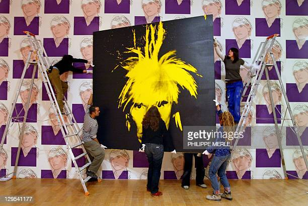 Workers prepare to hang an selfportrait of American artist Andy Warhol 26 January 2005 in the Lyon Contemporary Art Museum The Late Work on display...