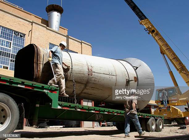 DENVER COLO AUGUST 10 2004 Workers prepare to lift one of four original smokestacks of the former Lowry Air Force Base Steam Plant back into position...