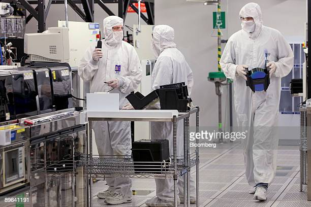 Workers prepare to load a silicon wafer machine in a clean room at the Texas Instruments semiconductor fabrication plant in Dallas Texas US on...