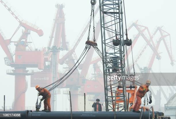 Workers prepare to load pipes onto a ship at the port in Lianyungang China's eastern Jiangsu province on January 14 2019 China's global trade volume...