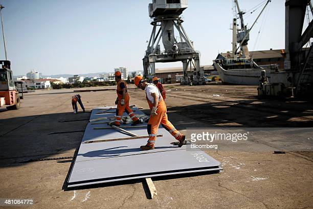 Workers prepare to load sheets of metal onto a cargo ship on the dockside at Thessaloniki port operated by Thessaloniki Port Authority SA in...