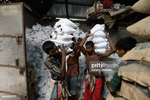 Workers prepare to load up rice sacks for food distribution for Rohingya refugees on September 30 2017 in Cox's Bazar Bangladesh Over 430000 Rohingya...